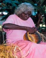 Aboriginal vrouw vlecht een mand in typische kleuren