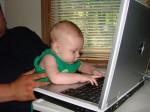 Voorbeeld van een baby die al wat mag spelen met een laptop